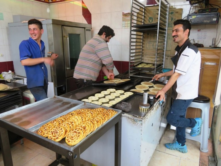 men in a bakery making klucheh fuman in Iran's