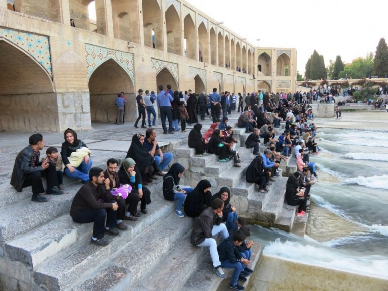 peopla at Khaju bridge enjoying the waters of the Zayandeh river in Isfahan Iran