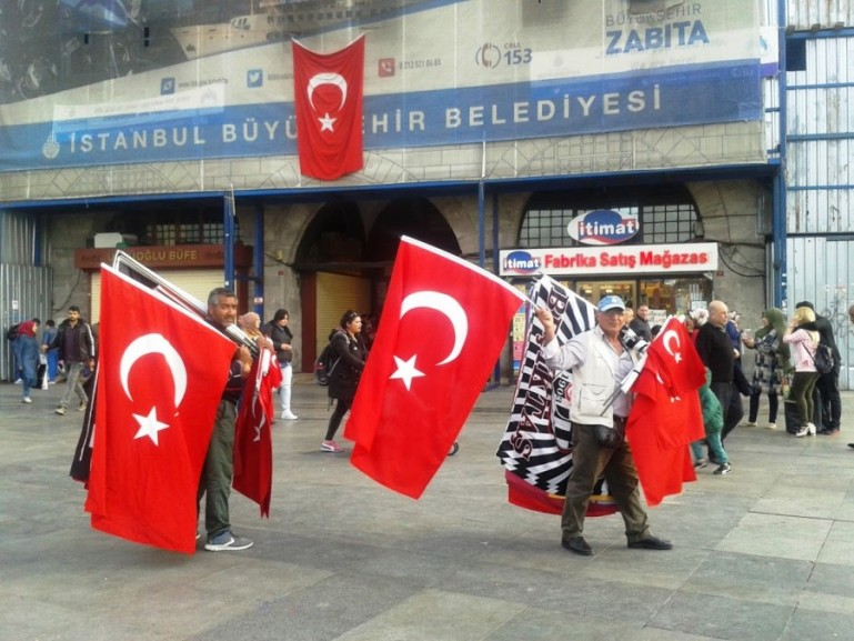 men selling Turkish flags near the Istanbul bazaar in Istanbul Turkey